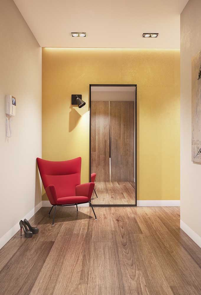 E que tal uma poltrona vermelha no corredor de parede amarela?