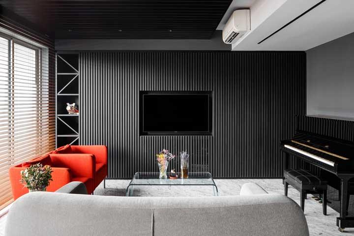 Aqui, a sala de estar preta ganhou vida com as poltronas vermelhas perto das janelas