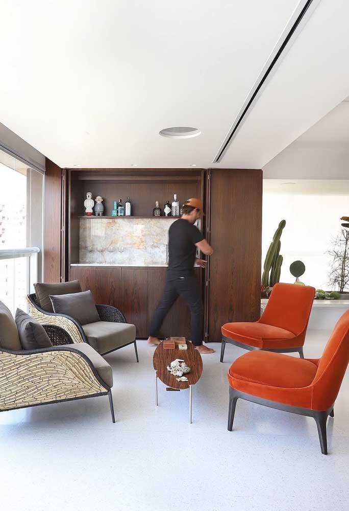 Aqui, o tom amadeirado dos móveis harmonizou muito bem com o tom de vermelho alaranjado das poltronas