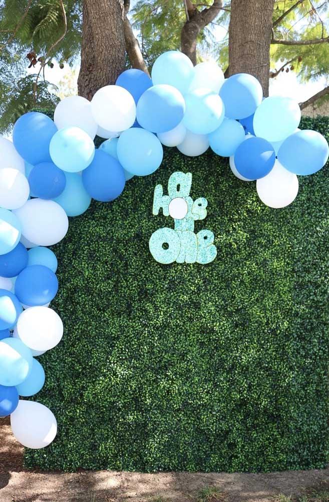Balões azuis e brancos decoram e contrastam o muro inglês para festa de aniversário infantil