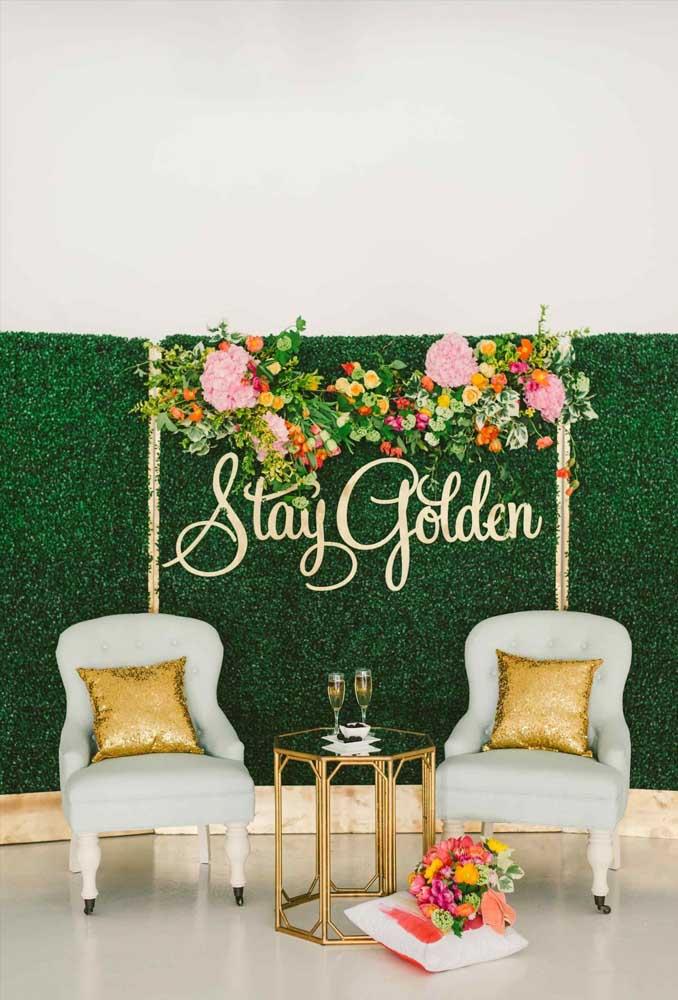 Cantinho especial da festa criado a partir do muro inglês decorado com flores