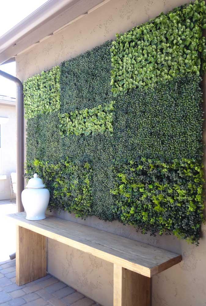 Aqui, o muro inglês artificial forma um quadro verde na parede do quintal da casa