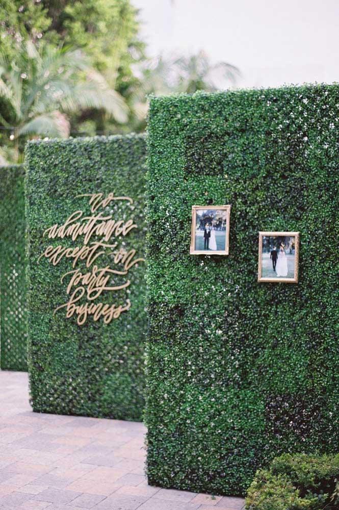 Conjunto de muro inglês adornando a entrada da festa de casamento. Junto com as folhagens foram usadas também fotos dos noivos
