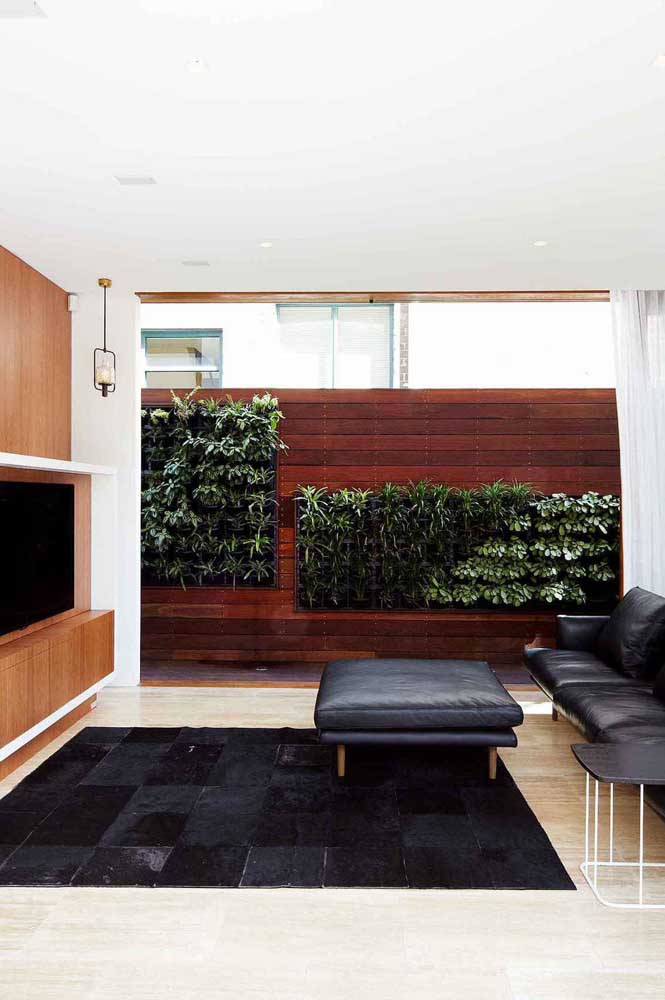 Mas se preferir, pode levar a ideia do muro inglês para a sala. Aqui, ele foi criado junto ao painel de madeira