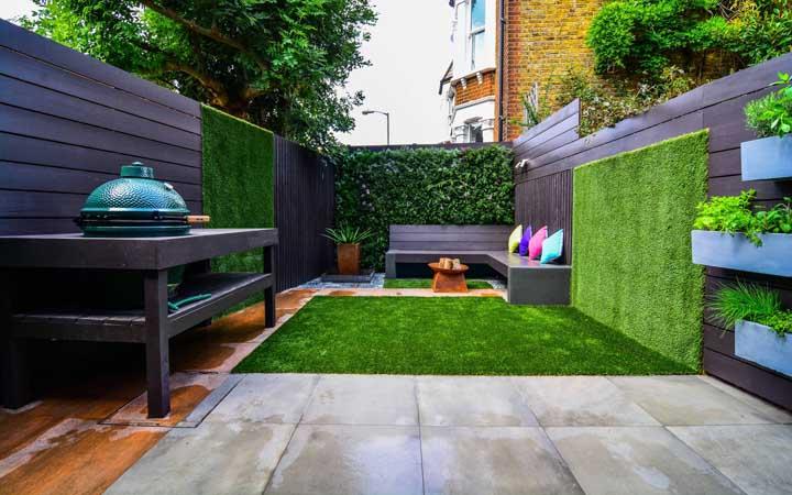 Duas ideias em um só quintal: muro inglês com grama sintética e, mais aos fundos, um muro inglês com folhas naturais