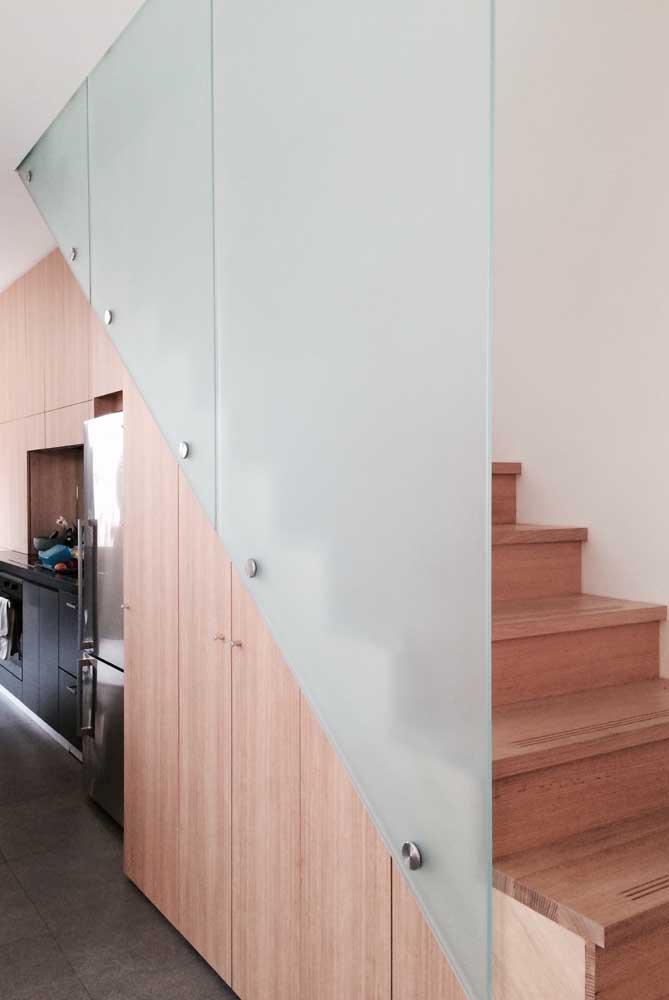 Já aqui, o vidro jateado faz a vez do tradicional guarda corpo da escada