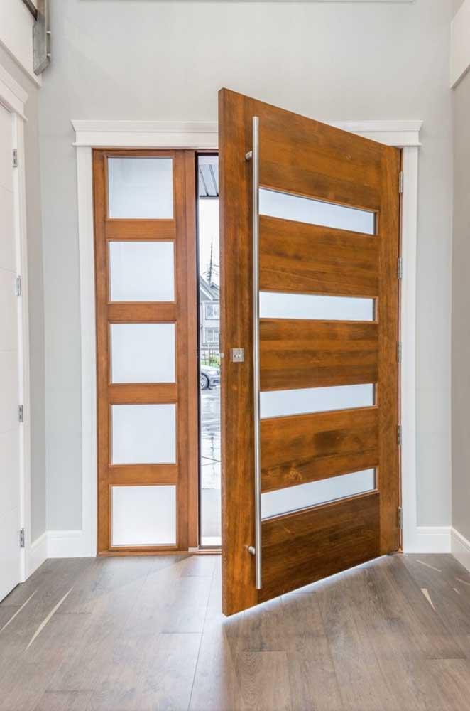 A porta de madeira maciça ganhou detalhes modernos com a aplicação dos detalhes em vidro jateado