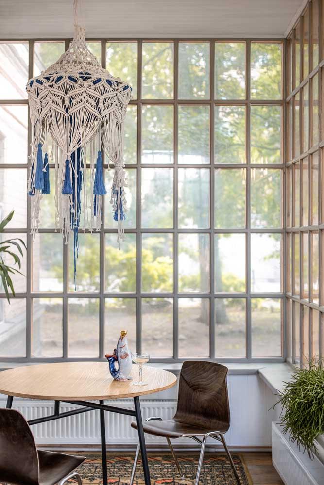 Entre a sala de jantar e a área externa está a janela com vidros jateados