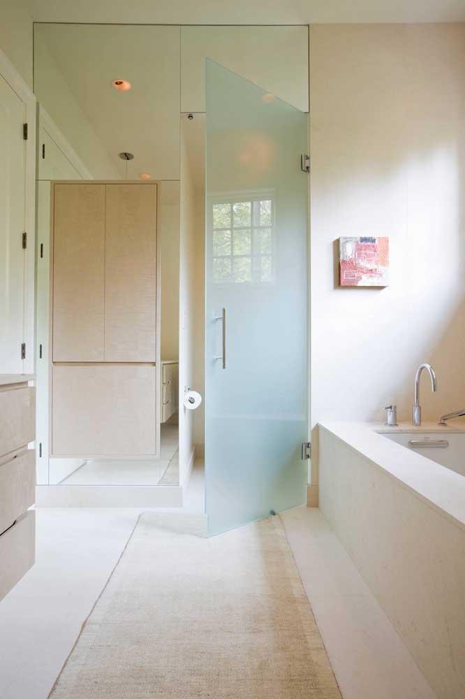 A parede com espelhos ganhou uma porta de vidro jateado que dá acesso a área do vaso sanitário