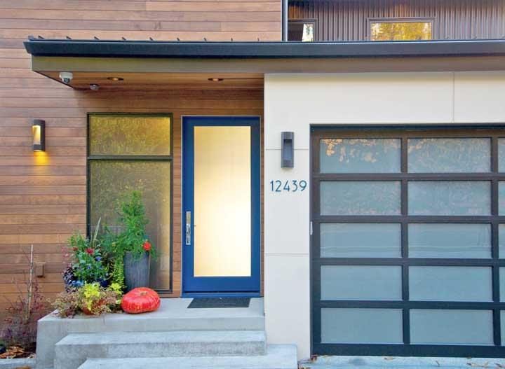 Essa fachada ficou incrível com a porta de moldura azul e vidro jateado