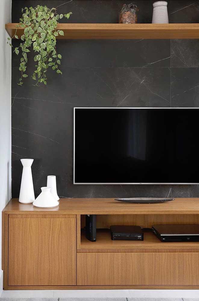 Parede preta na sala de estar. Móveis de madeira valorizam a composição