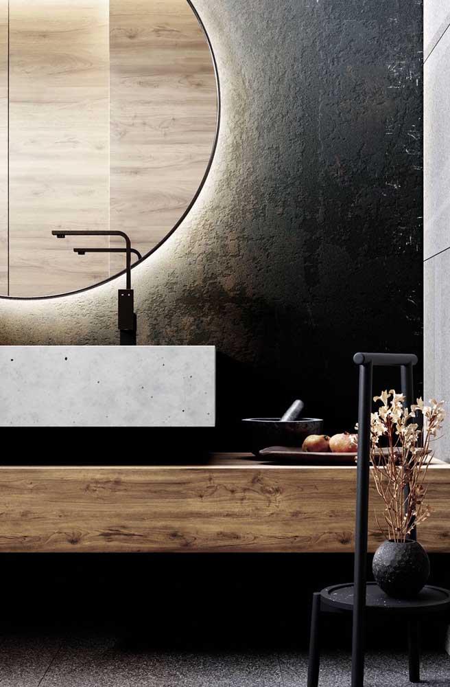 Agora é a vez do banheiro ganhar uma parede preta e rústica com iluminação indireta