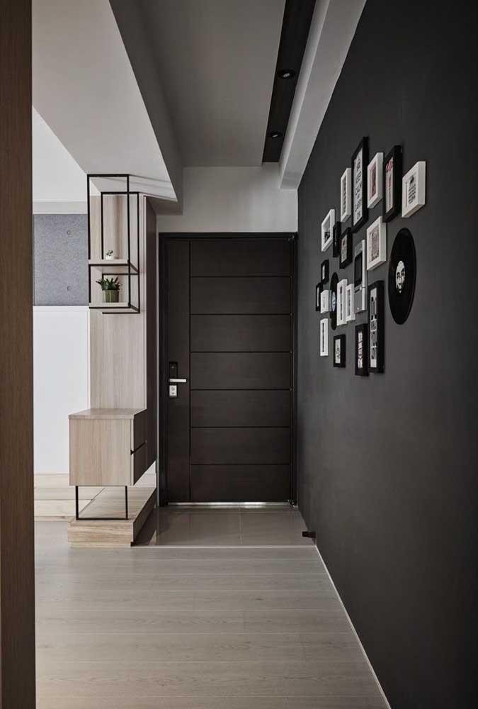 Parede preta para marcar o corredor da casa. Quadros e fotografias ajudam na decoração do espaço