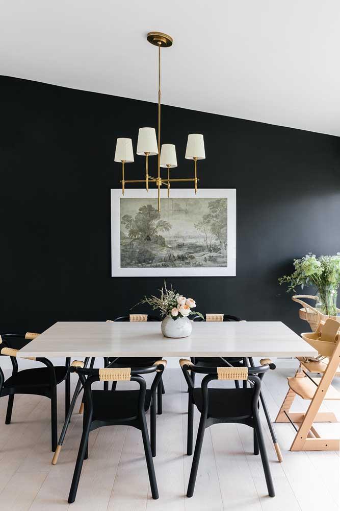 Nessa sala de jantar, a parede preta destaca as linhas arquitetônicas da casa, causando um efeito visual bem inusitado