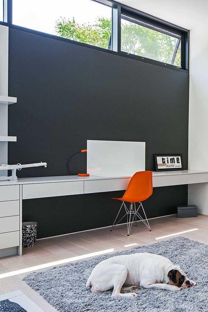 O lindo contraste entre o preto da parede e o tom de laranja da cadeira