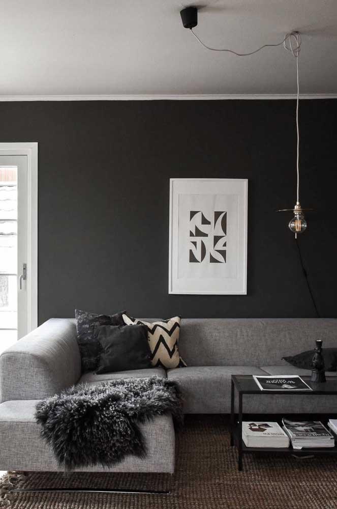 Parede preta na sala de estar em harmonia com a paleta de cinza e branco que predomina no restante do ambiente