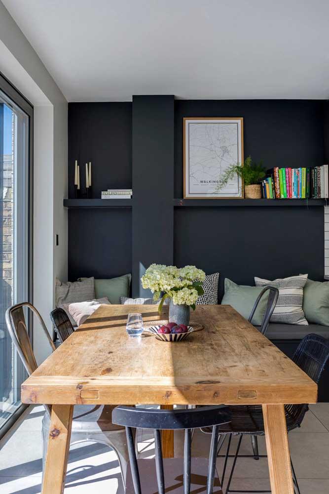 Sala de jantar com paredes pretas e mobiliário de madeira