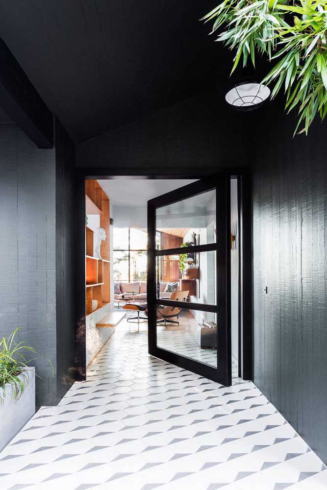 Aqui, o hall de entrada também traz paredes pretas, mas com o diferencial da porta estar na mesma cor