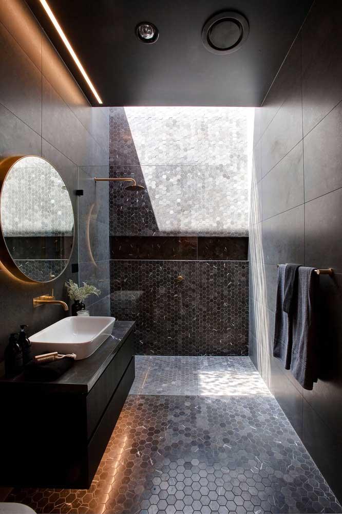 Aqui, o banheiro todo preto é contrastado pelo projeto de iluminação que abraça tanto a luz natural, quanto a artificial