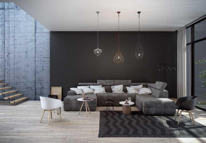 Sala de estar com parede preta. As luminárias pendentes se destacam na frente da parede