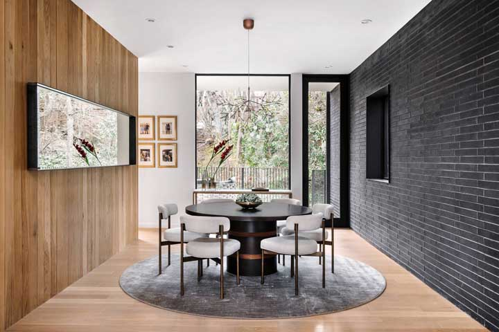 Sala de jantar com parede preta. A mesa na mesma cor completa o visual
