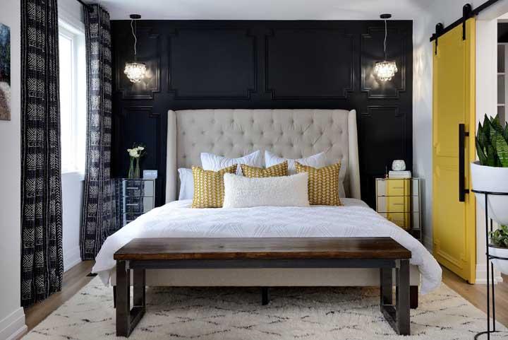 Um quarto de casal com parede preta e detalhes em amarelo. Personalidade e alto astral