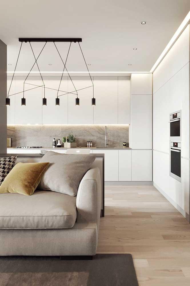 Cozinha americana integrada com a sala de estar. Repare que os tons claros favorecem a sensação de amplitude