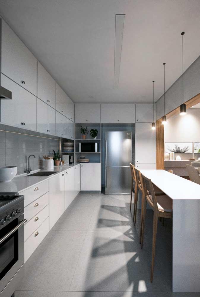 Cozinha americana em formato retangular muito bem aproveitada com armários aéreos