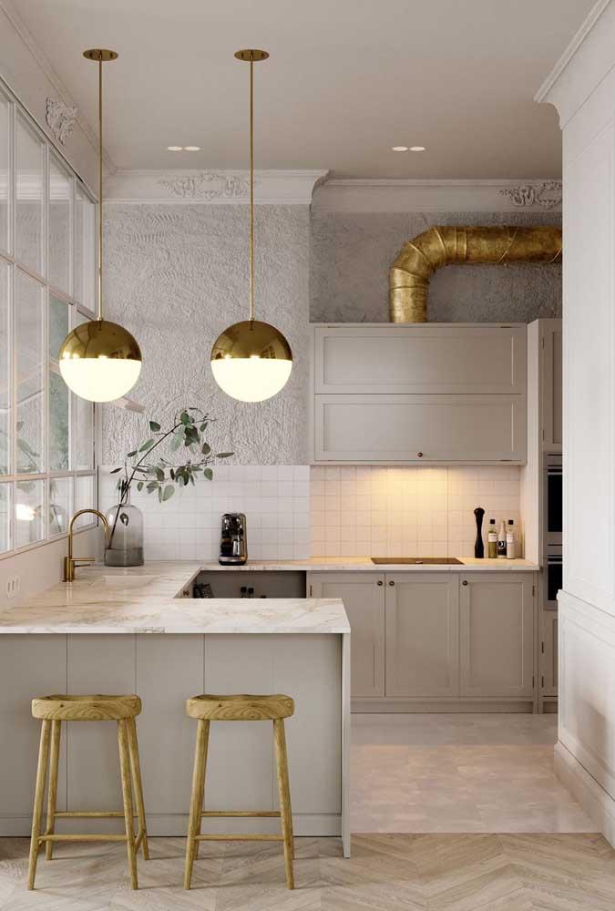 Cozinha americana em L com detalhes luxuosos de mármore e dourado