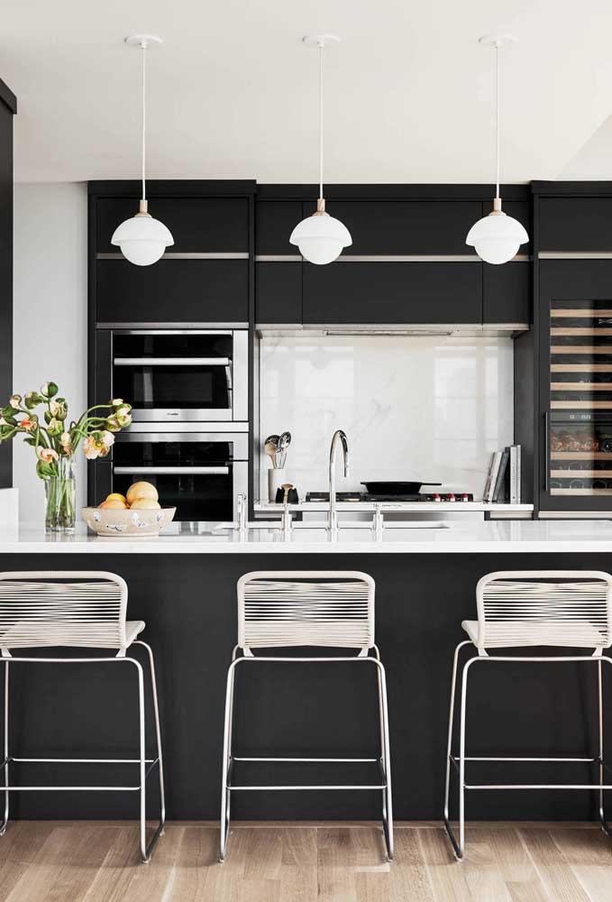Aqui, a cozinha americana preta ganhou detalhes em inox para se iluminar