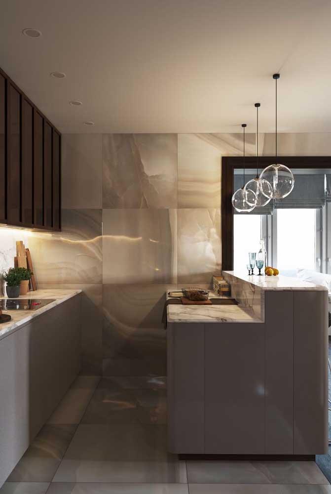 Cozinha americana com bancada e balcão integrados. O mármore trouxe um toque de sofisticação ao projeto