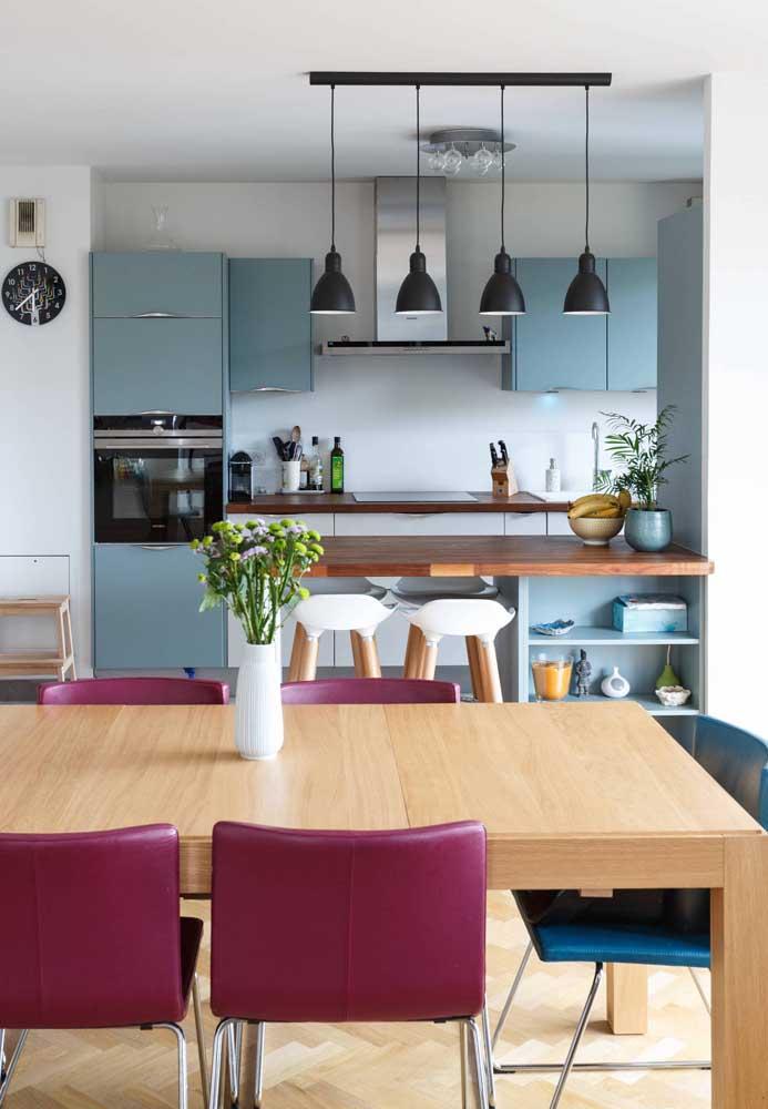 Cozinha americana parcialmente integrada pelo balcão de madeira. A cor alegre dos armários chama atenção por aqui