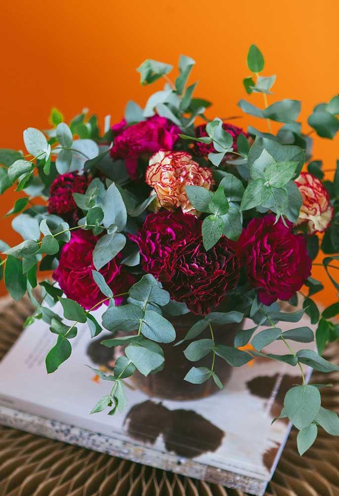 Arranjo de flores feito com cravos roxos e laranjas