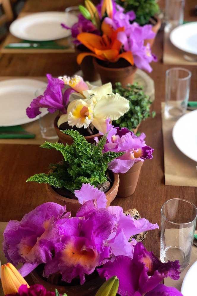 Orquídeas de cores vibrantes e alegres enchem a mesa posta do casamento