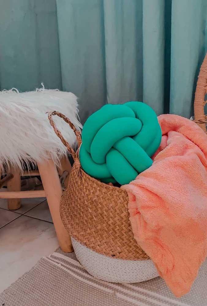 O cestinho da sala acomoda de tudo, incluindo a almofada de nó verde