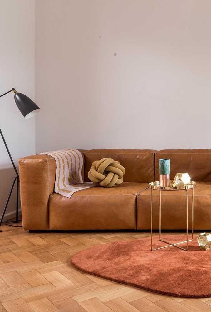 Nessa sala, o sofá de couro recebeu muito bem a almofada de nó mostarda