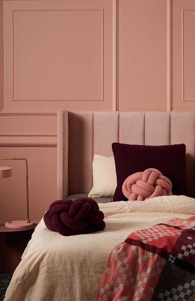 Sobre a cama do casal destacam-se as almofadas de nó compondo um tom sobre tom