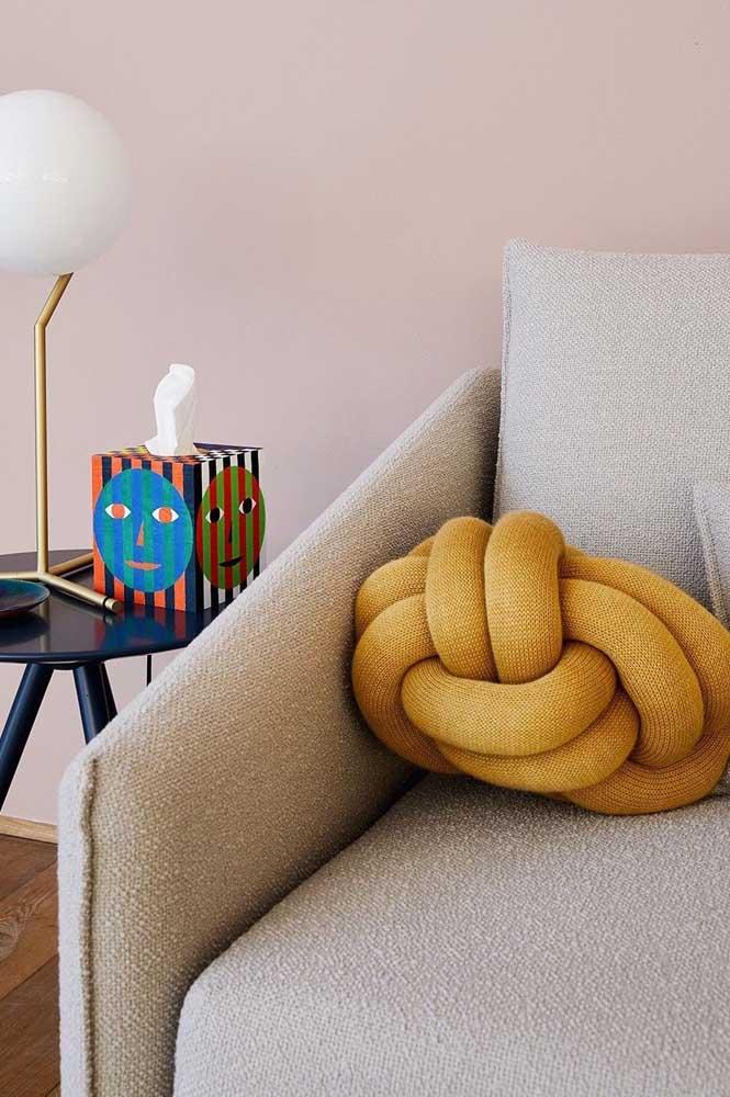 Almofada de nó para o sofá. O tom mostarda ajuda a destacar a peça na decoração