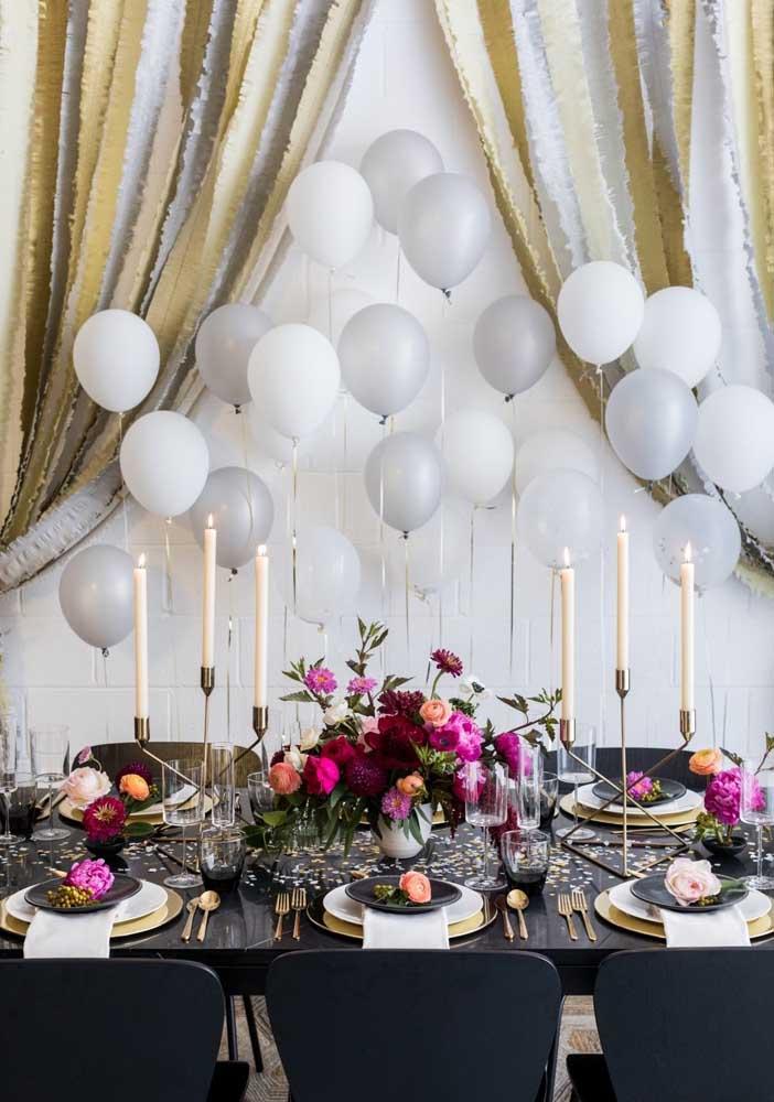 Já aqui você confere a mesa posta para a festa surpresa. Balões, castiçais e flores garantem o charme da decor