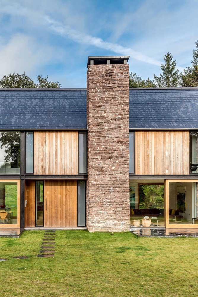 Olha que belo mix de contrastes: telha shingle preta, pedras, madeira e vidro