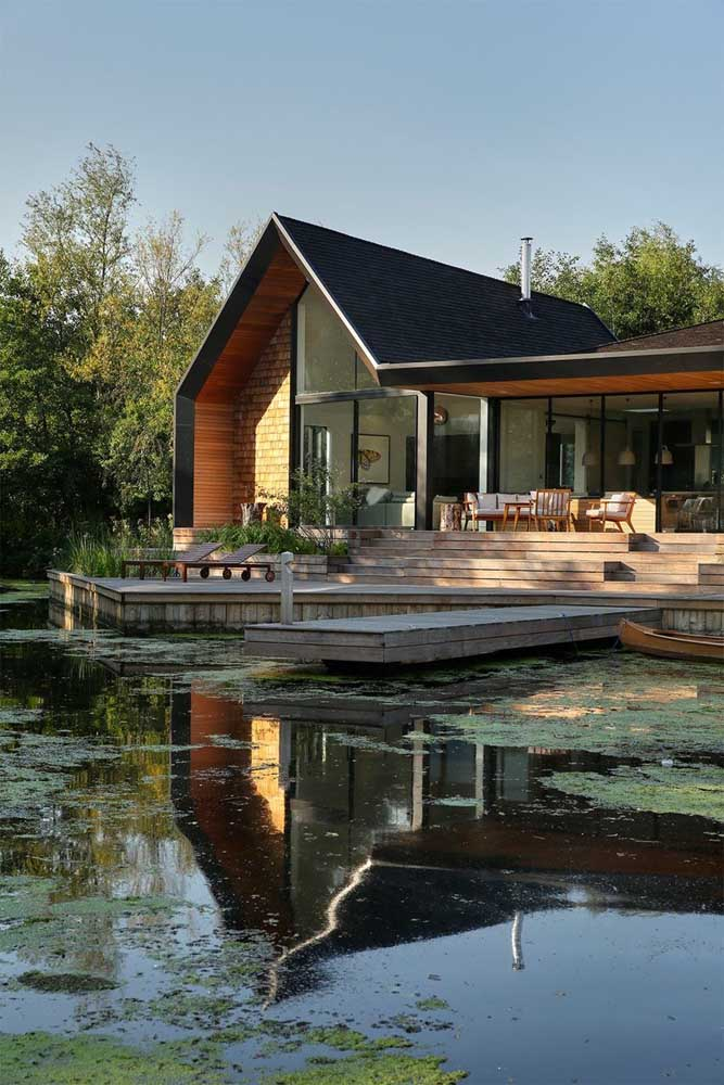 Um luxo essa casa na beira do lago com telhado de telhas shingle pretas