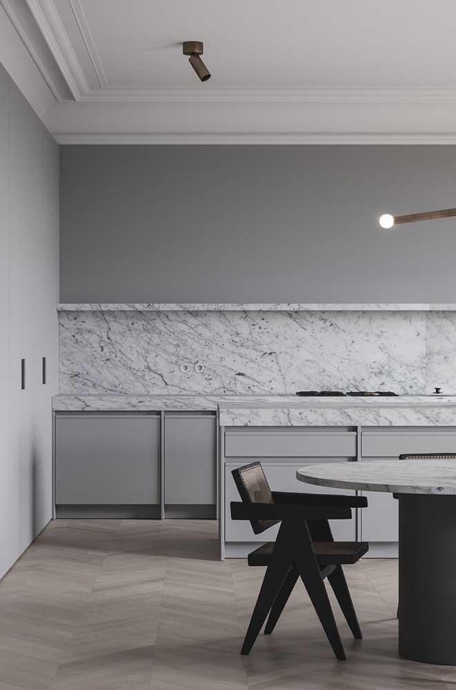 Nessa cozinha, o mármore é rei. Repare que a pedra foi usada na bancada da pia, na parede e no tampo da mesa