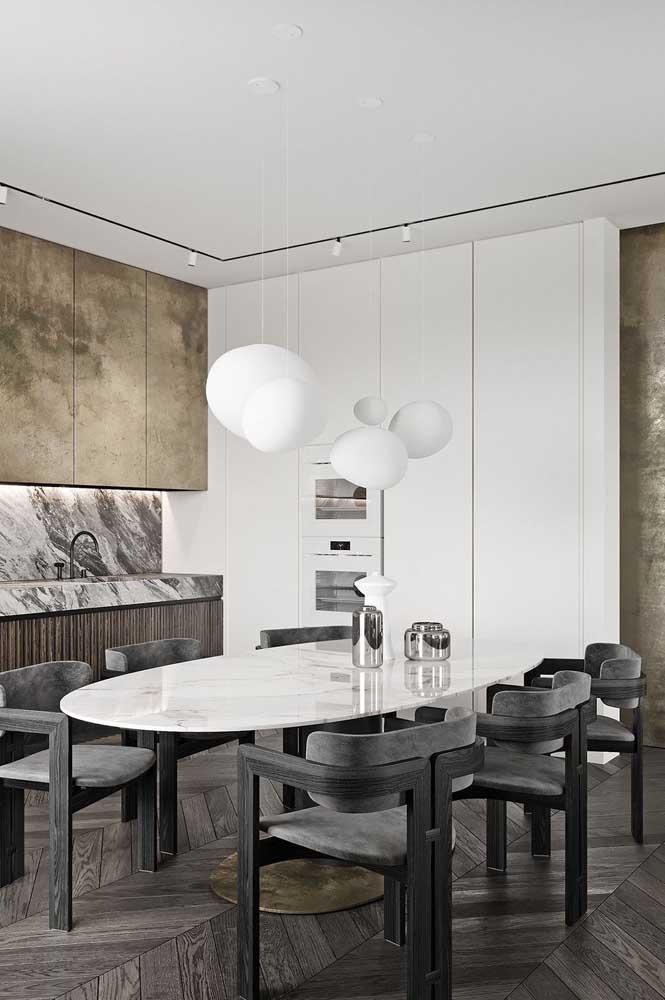 Mesa de mármore branco em formato oval para sala de jantar. As cadeiras pretas fecham a composição