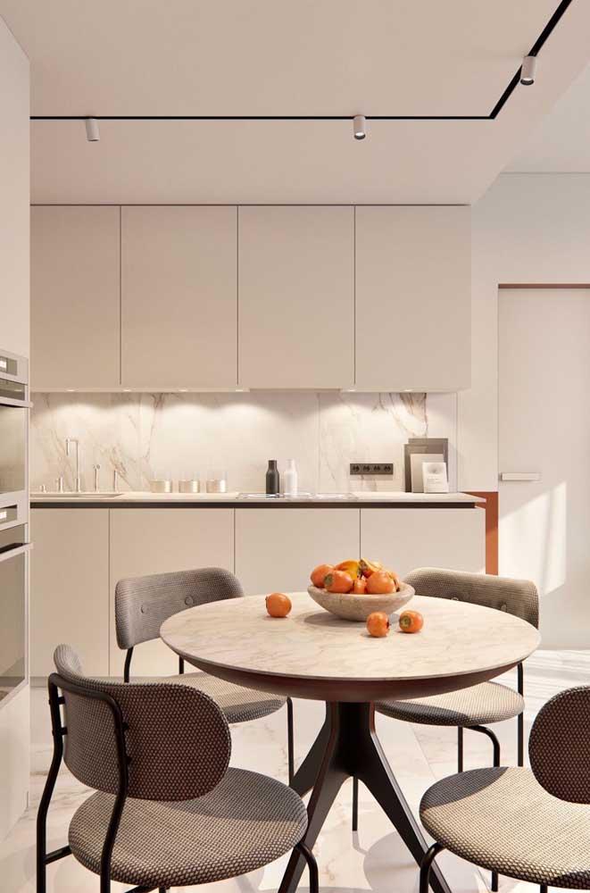 Mesa de jantar redonda com quatro lugares. O tampo de mármore confere a elegância necessária ao ambiente