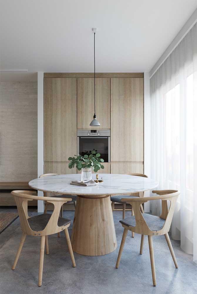 A combinação entre tampo de mármore e base de madeira forma uma mesa acolhedora e convidativa