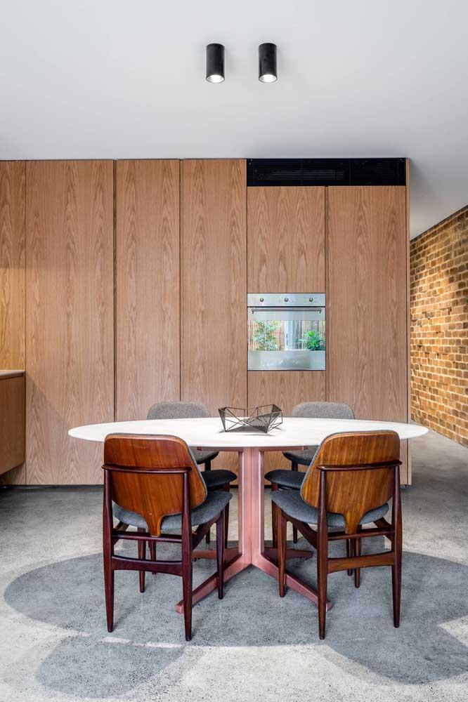 Mesa de mármore redonda com quatro lugares. A estrutura de madeira é um charme a parte