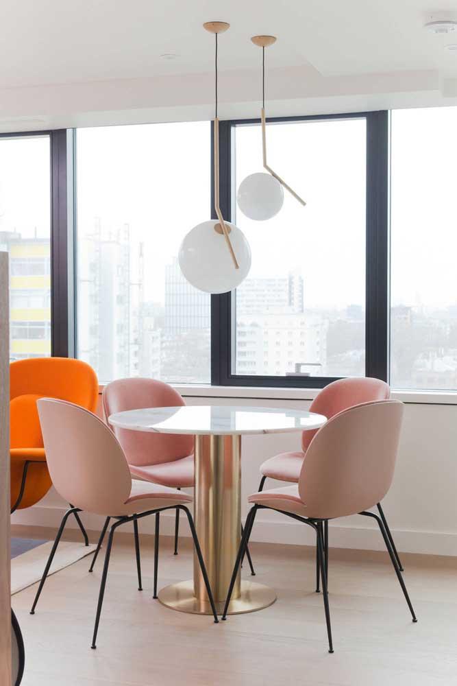 Glamorosa e elegante, a mesa de mármore ganhou pé dourado e a companhia de cadeiras modernas