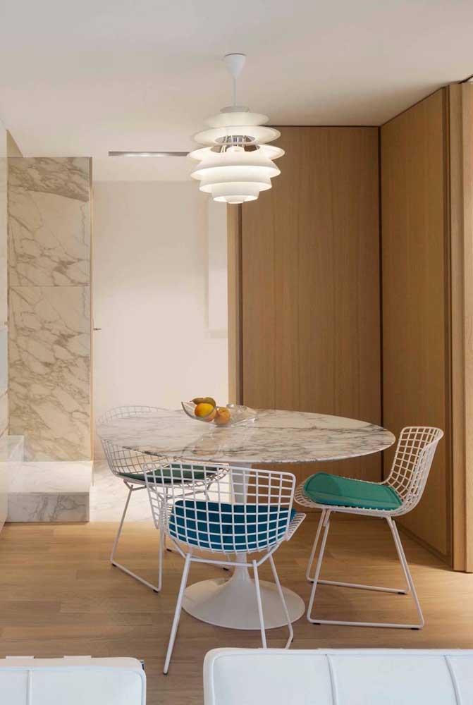A pequena sala de jantar ganhou uma mesa de mármore redonda acompanhada de cadeiras aramadas