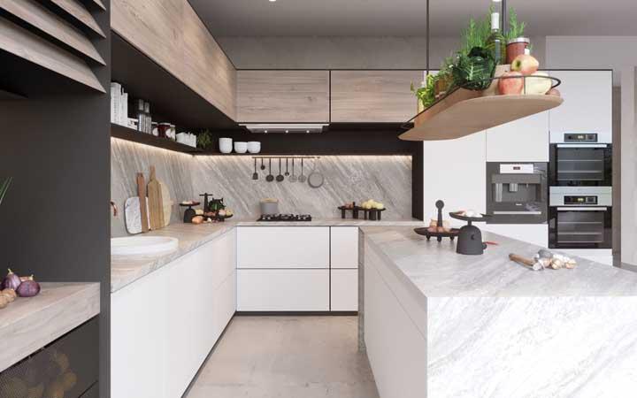 Cozinha planejada com mármore em todas as superfícies - ilha e bancada, além do revestimento da parede