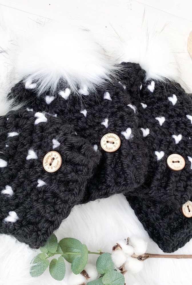 Touca de crochê preta com mini corações brancos. Os pompons e os botões completam o visual da peça